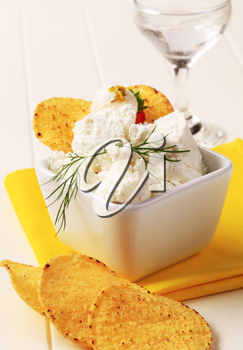 Corn chips and bowl of curd cheese