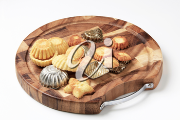Small tart shells and baking pans on a cutting board