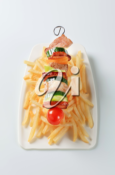 Pork and vegetable skewer with French fries