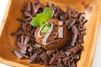Scoop of ice cream and chocolate shavings in wooden bowl