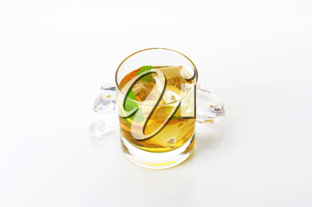 glass of apple juice with mint and ice on white background