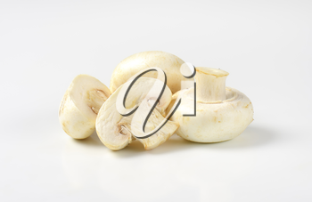 Whole and halved raw white mushrooms