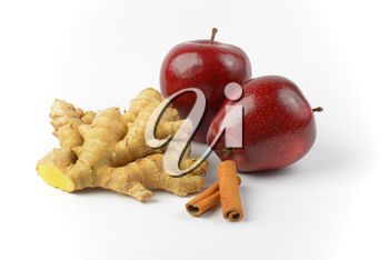 two fresh red apples, ginger root and cinnamon sticks
