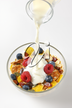 milk pouring into bowl of breakfast cereals with berry fruit