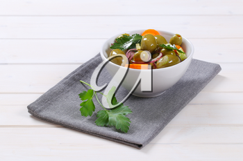bowl of vegetable salad with pickled green olives on grey place mat