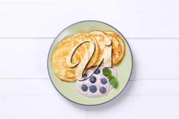 plate of american pancakes with yogurt and fresh blueberries on white wooden background