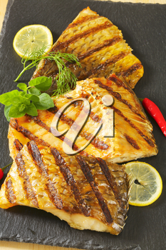 Grilled carp fillets with lemon, herbs and red chili pepper