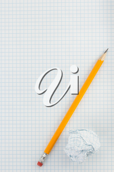 pencil and crumpled paper ball on checked background