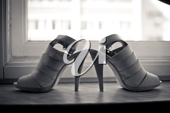 Shoes on a window sill. Wedding shoes in it are black - white tones.