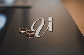 Wedding rings lie on a smooth table.
