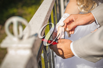 Newly-married couple closes the lock fortunately.