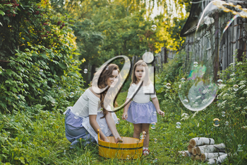 Daughter with mother blowing bubbles in the nature.