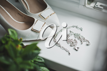 Crystal earrings and white shoes.