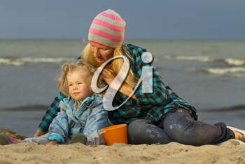 Mother and daughter sitting at the sea . early autumn , end of summer . Family vacation by the sea
