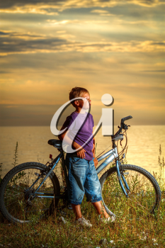 boy on a bicycle near the sea in the evening at sunset. summer vacation