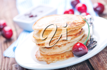 pancakes with cherry on the plate and on a table
