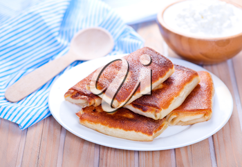 pancakes with cottage and sour cream on a table