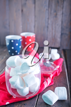 white marshmallows in glass bank and on a table