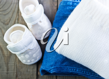 baby clothes on the wooden table, shoes for baby
