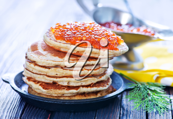 pancakes with red salmon caviar on plate
