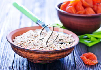raw oat flakes with dry apricots in the bowl