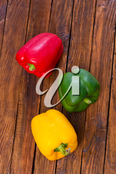 color peppers on the wooden table, red and yellow peppers