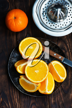 fresh oranges on the wooden board and on a table