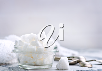 white sugar in glass bowl and on a table