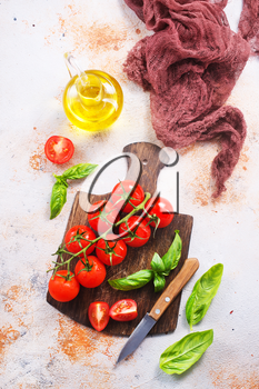 fresh tomato with green basil on a table
