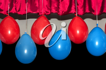 Red and blue balloons on a dark background