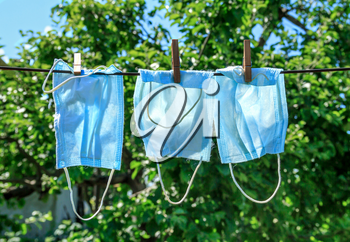 Three used washing face masks drying on a sunny day