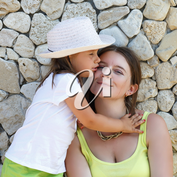 Hugging mother and daughter. Smiling woman and baby girl in white hat. An old stone wall in the background.