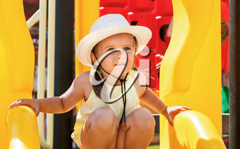 Portrait of a baby in a white hat and a yellow t-shirt on the playground on a sunny day. Shallow depth of field. Focus on model.