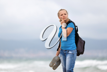 Pretty young blonde woman in a blue t-shirt and jeans with a backpack standing on a sea background.  Shallow depth of field. Focus on model.