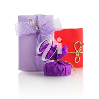 Three bright multi-colored gift boxes on a white background with reflection. Isolated with clipping path. Shallow depth of field.
