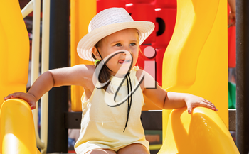A child in a white hat and a yellow t-shirt on the playground on a sunny day. Shallow depth of field. Focus on the model's face.