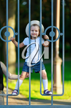 Happy child climbs on the bars of a metal fence. Warm sunny summer day. Vertical shot.