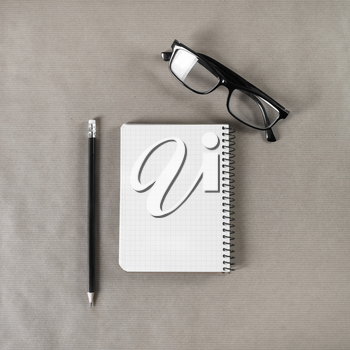 Blank notebook, glasses and pencil on craft paper background. Mock up for graphic designers portfolios. Stationery template. Top view.
