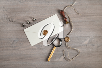 Vintage letter envelope with golden wax seal, stamp and magnifier, at wood table background. Mock-up for your design. Flat lay.