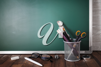 Photo of school stationery on blank green chalkboard background. Copy space for text.