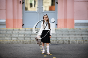 Child girl with plush toy against school background. Back to school. Selective focus.