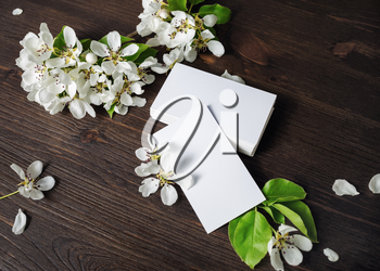 Photo of blank white business cards and flowers on wooden background. Template for ID.