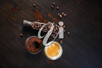Photo of coffee espresso cup, roasted coffee beans and ground powder against wooden table background. Top view. Flat lay.
