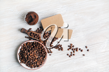 Coffee beans, blank kraft business cards and coffee ground on light wood table background. Top view. Flat lay.