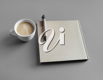 Closed booklet, coffee cup and pen on gray paper background.
