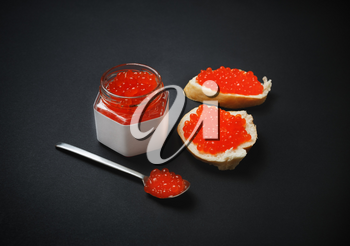 Fresh deliciousd caviar. Sandwiches with red caviar, glass jar and spoon on black background.