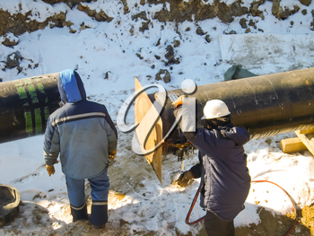 The workers engaged in the construction of the pipeline. Welders build the pipeline. Installation work in the construction and installation of the pipeline.