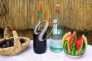 Bottles of wine and moonshine on the table. A basket with a plum and a watermelon as a snack. Traditional alcoholic drinks.