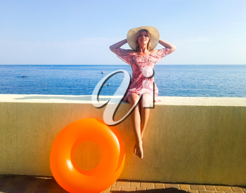 A woman with a beautiful figure is sitting on a concrete fence in front of the sea. Nogshinahschiny orange inflatable circle