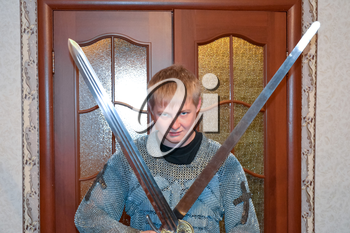 A man dressed up in a knight's hauberk at home in his room. Knight's sword in the hands of a man. Knightly chain armor and sword. Fitting of a knightly armor.
